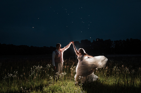 bride and groom dancing in a field after their wedding.