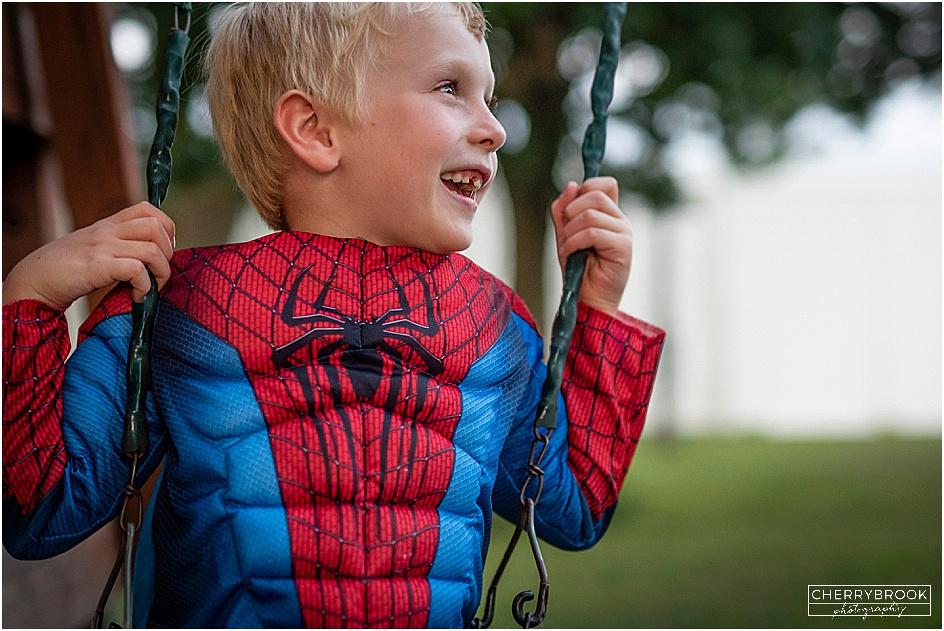 Smiling children wearing super hero costumes.